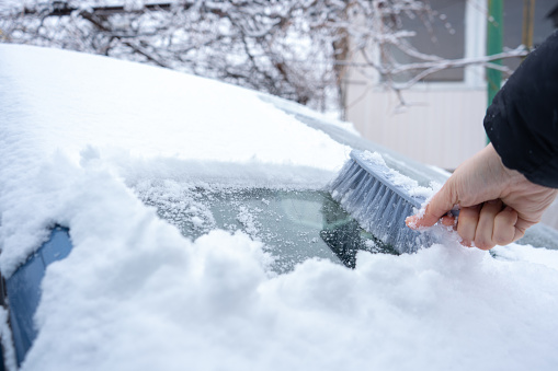 Clearing snow from the car windshield with car brush