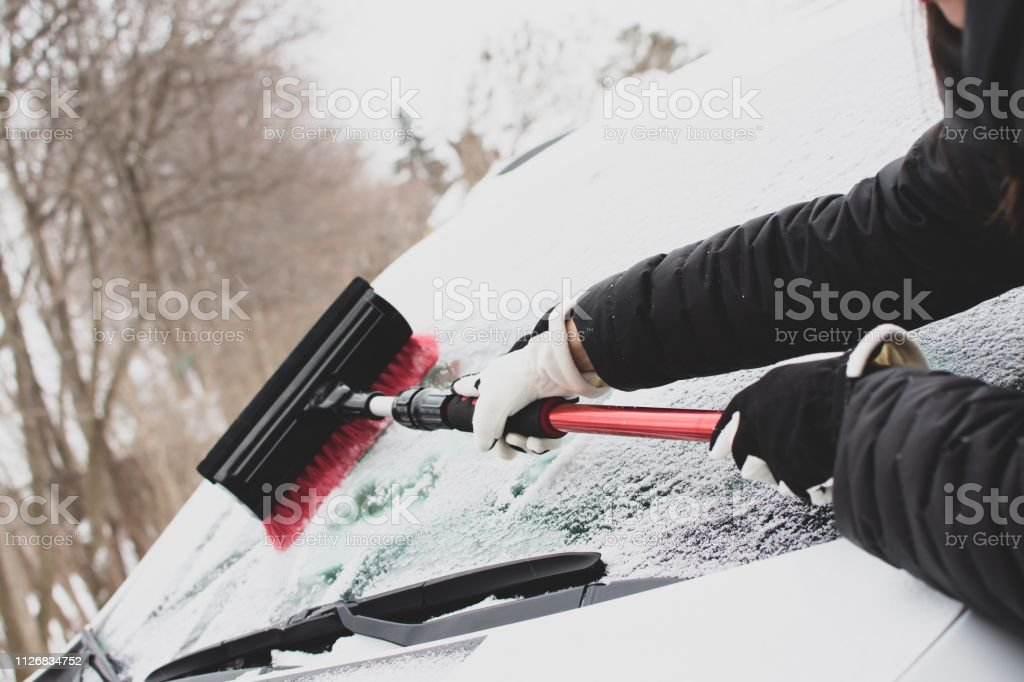 Clearing snow off car windshield after winter storm stock photo