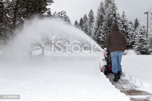 A man uses his snow blower to clear the driveway after a snowstorm.