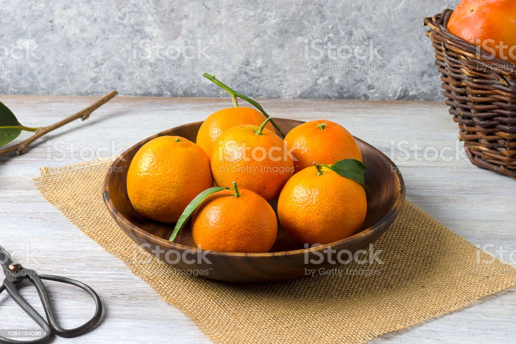 Clementines in a wooden basket, on a rustic wooden background - foto stock