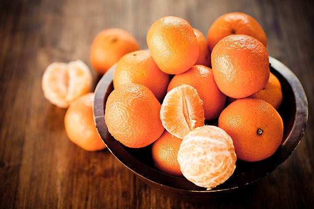 Clementines Citrus fruit: Clementines in a rustic wooden bowl. tangerine stock pictures, royalty-free photos & images