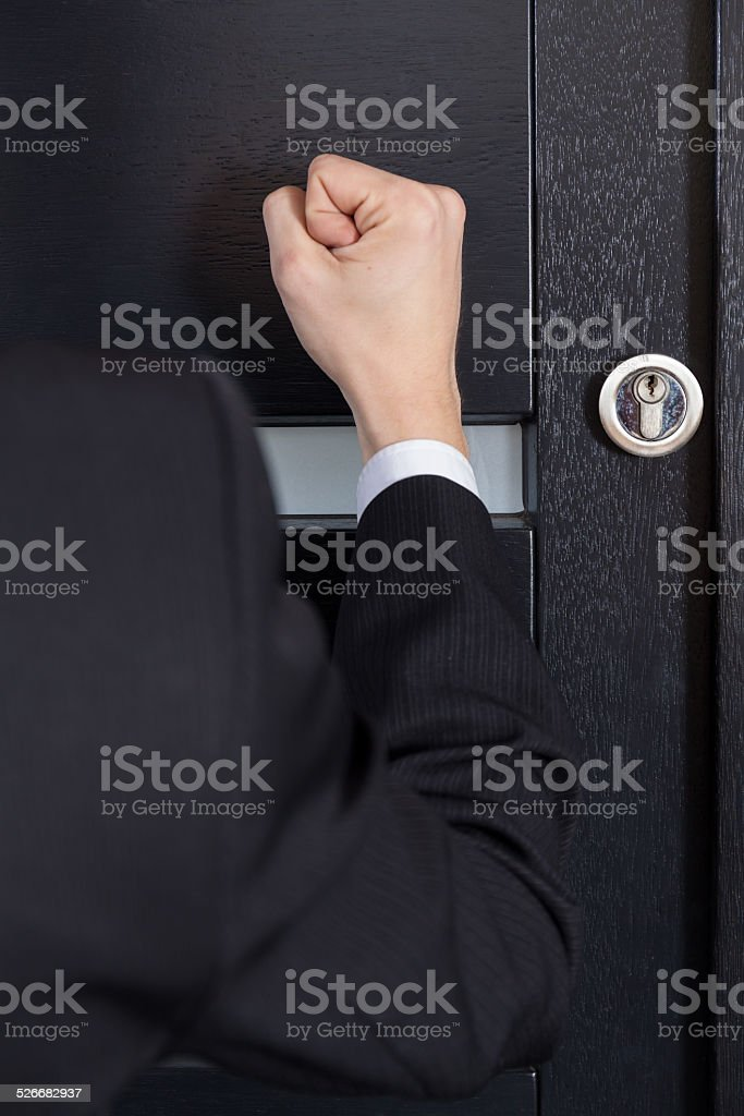 Clenched fist knocking stock photo