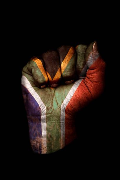 Geballte Faust mit der südafrikanischen Flagge gemalt, isoliert auf Schwarz – Foto