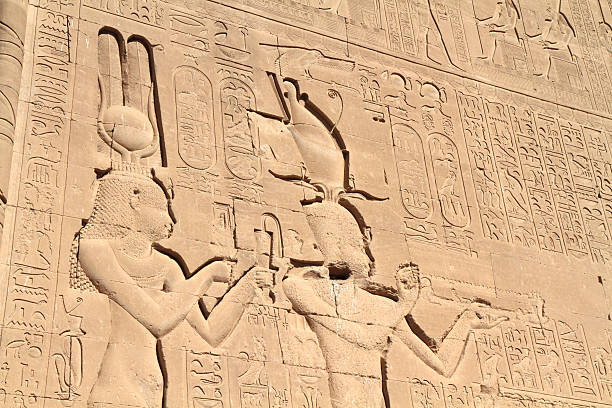 """Cleopatra and Caesarean, Temple of Hathor, Dendera, Egypt """"Massive sunk relief of Cleopatra (Cleopatra VII) and her son Caesarean decorates the south wall of the Temple of Hathor, Dendera, Egypt.  Cleopatra wears the solar disk and horns associated with the goddess Hathor as well as the Atef crown while Caesarean wears the double crown of Egypt (the Pschent).  Dedicated to Hathor, goddess of love, beauty, music and motherhood, the main temple dates from the Graeco-Roman era although a temple stood on the site during the Old Kingdom."""" greco roman style stock pictures, royalty-free photos & images"""