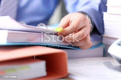 istock Clerk arm bend over pages in pile of bookmarked documents 1133125586