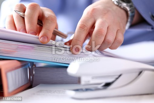 istock Clerk arm bend over pages in pile of bookmarked documents 1133125599