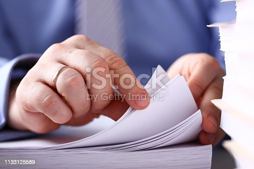 istock Clerk arm bend over pages in pile of documents closeup 1133125589