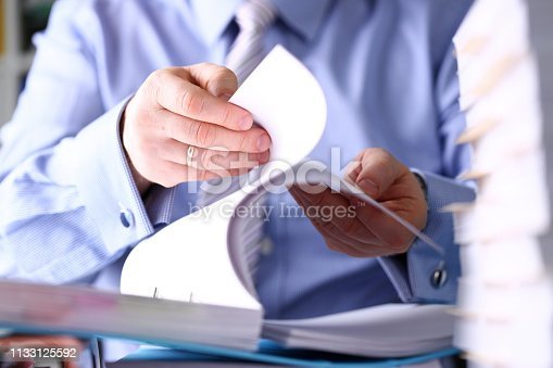 istock Clerk arm bend over pages in pile of documents closeup 1133125592