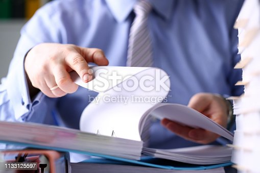 istock Clerk arm bend over pages in pile of documents closeup 1133125597