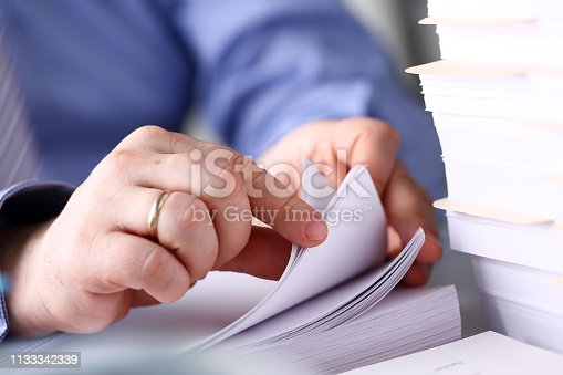istock Clerk arm bend over pages in pile of documents closeup 1133342339