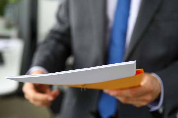 Clerk hand in suit and tie holding yellow envelope containing batch of important papers stock photo