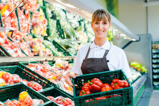 Clerk in a supermarket showing fresh vegetables stock photo