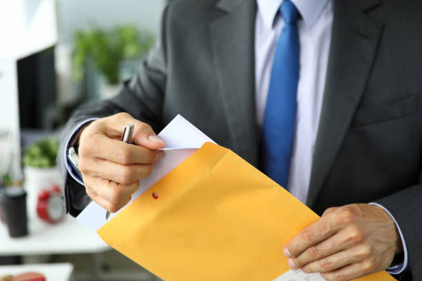 Clerk in suit and tie at workplace packing envelope unpacking envelope with important documentation stock photo