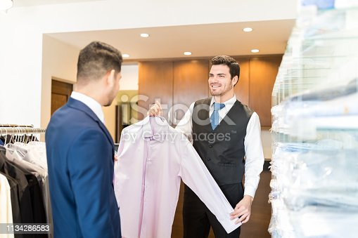 istock Clerk Showing Formal Shirt To Customer 1134286583