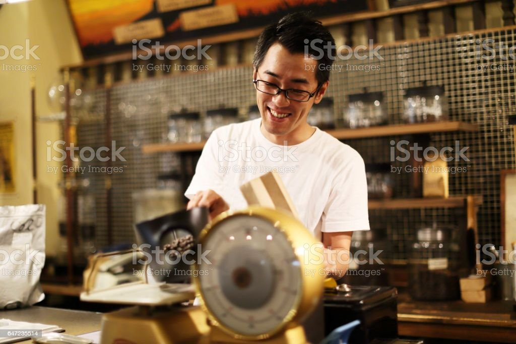Clerk to measure the coffee beans while the service stock photo