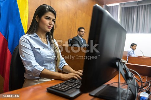 Clerk typing the session in trial at the courtroom - legal system concepts