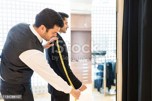 istock Clerk Using Tape Measure In Shop 1134288107