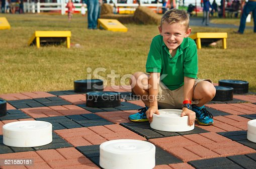 Clever young boy playing a life size checkers game outside on an autumn day at a festival.