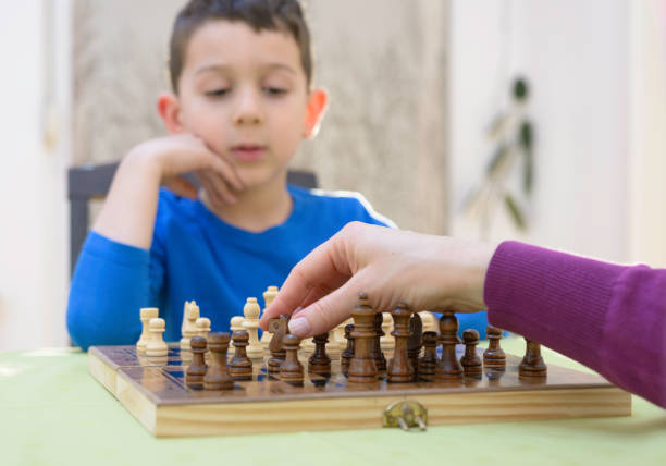 Cleveres Kind ist konzentriert und denkt, während man Schach spielt – Foto