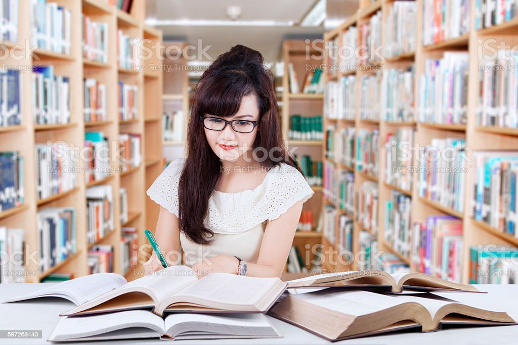Clever learner doing school task in library royalty-free stock photo