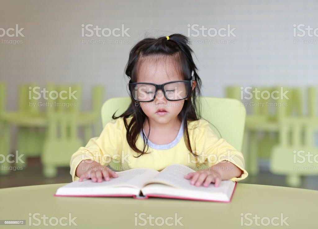 6cee29c0cda297 Slim kind meisje met bril lezen van een boek in de kinderkamer. royalty  free stockfoto