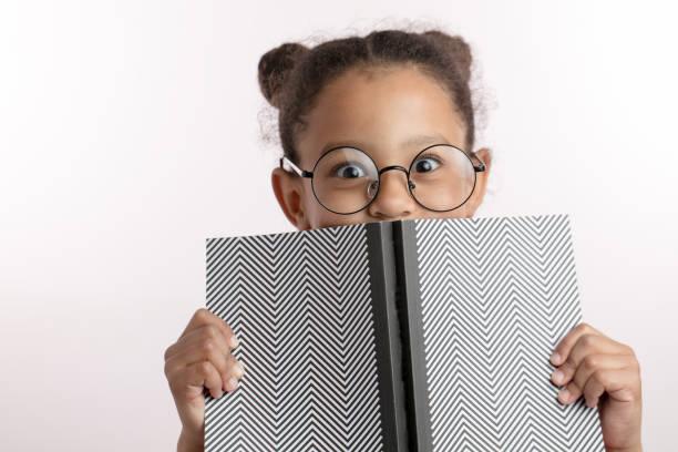 slim meisje met hairbunds en ronde glazen verstopt achter het kladblok - a little girl reading a book stockfoto's en -beelden