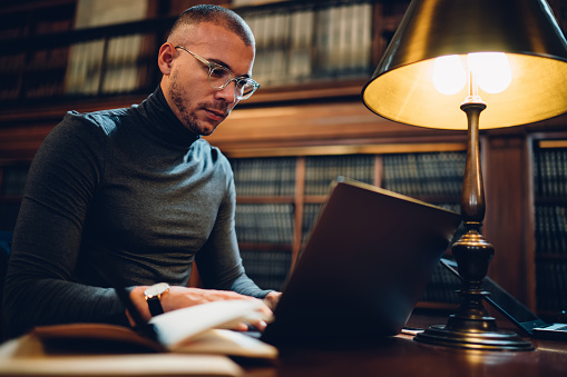 istock Clever male writer concentrated on idea for bestseller working in library with wifi connection and book archive, young professor in spectacles analyzing information for project making research 1158476129
