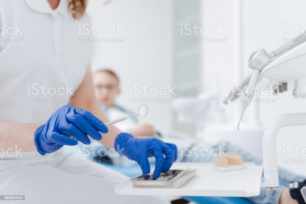 Clever neat dentist taking her tools 免版稅 stock photo