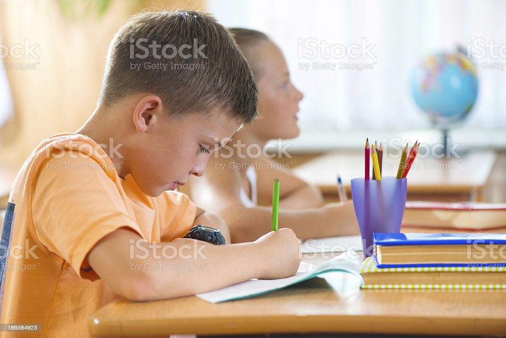 Clever schoolboy studying in classroom royalty-free stock photo