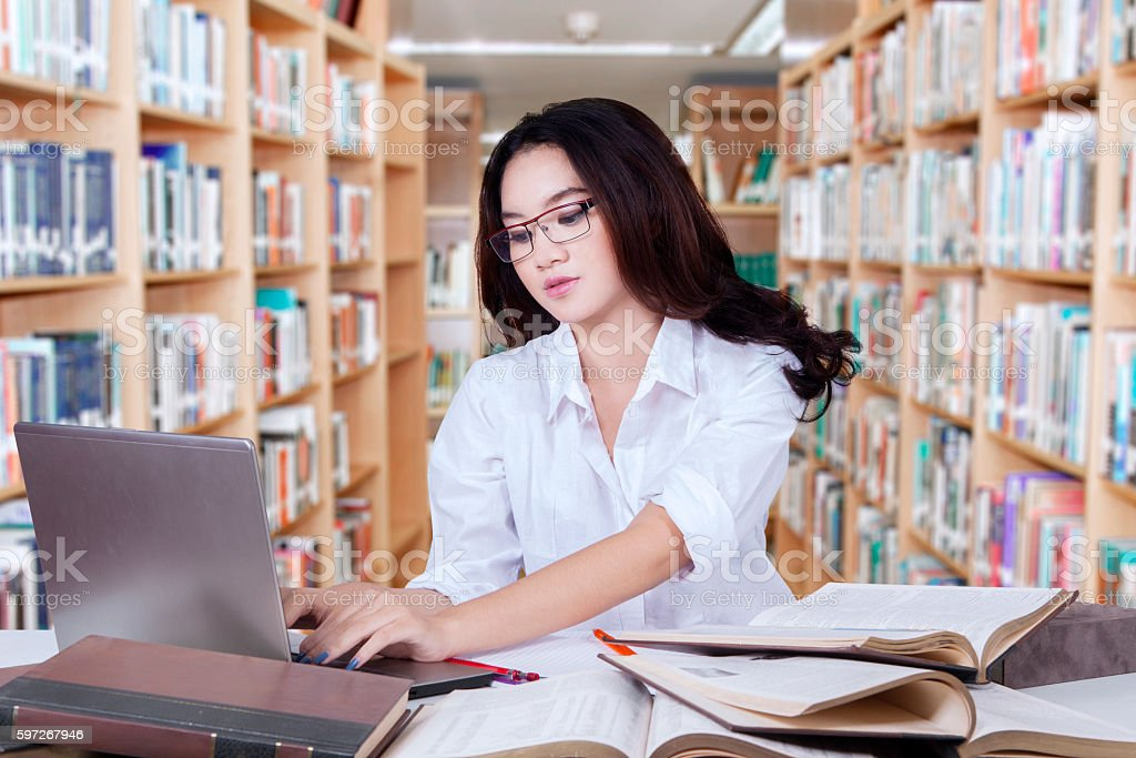 Clever student with long hair studying in library royalty-free stock photo