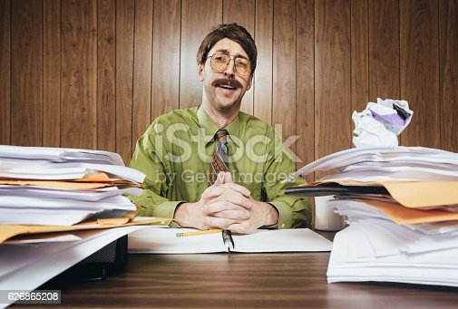 A white collar business man working in a retro 1980's style office sits at a desk piled with paperwork and documents.  He looks at the camera with a cheesy smile while making his sales pitch.