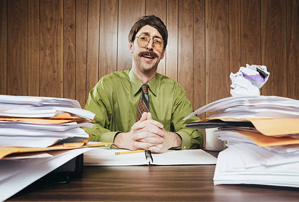 Cliche Office Salesman A white collar business man working in a retro 1980's style office sits at a desk piled with paperwork and documents.  He looks at the camera with a cheesy smile while making his sales pitch. salesman stock pictures, royalty-free photos & images