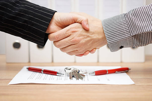 client and agent are handshaking over real estate contract - estate agent sign stock photos and pictures