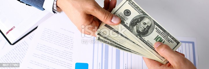 863128060 istock photo Client arm give pack of hundred dollars bills 863127980