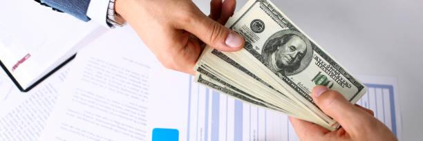 brazo del cliente dar paquete de billetes de cien dólares - indemnización compensación fotografías e imágenes de stock