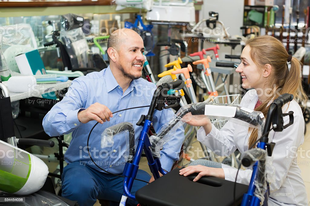 Client asking girl about electric wheelchairs stock photo