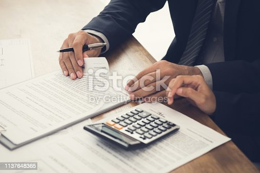 istock Client consulting with agent, reviewing an agreement about to sign 1137648365