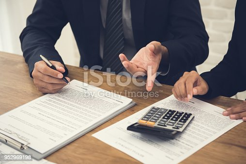 istock Client consulting with agent, reviewing an agreement about to sign 952969198