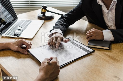 istock client customer signing contract and discussing business with legal consultants, notary or justice lawyer with laptop computer and wooden judge gavel on desk in courtroom office, legal service concept 1144544438