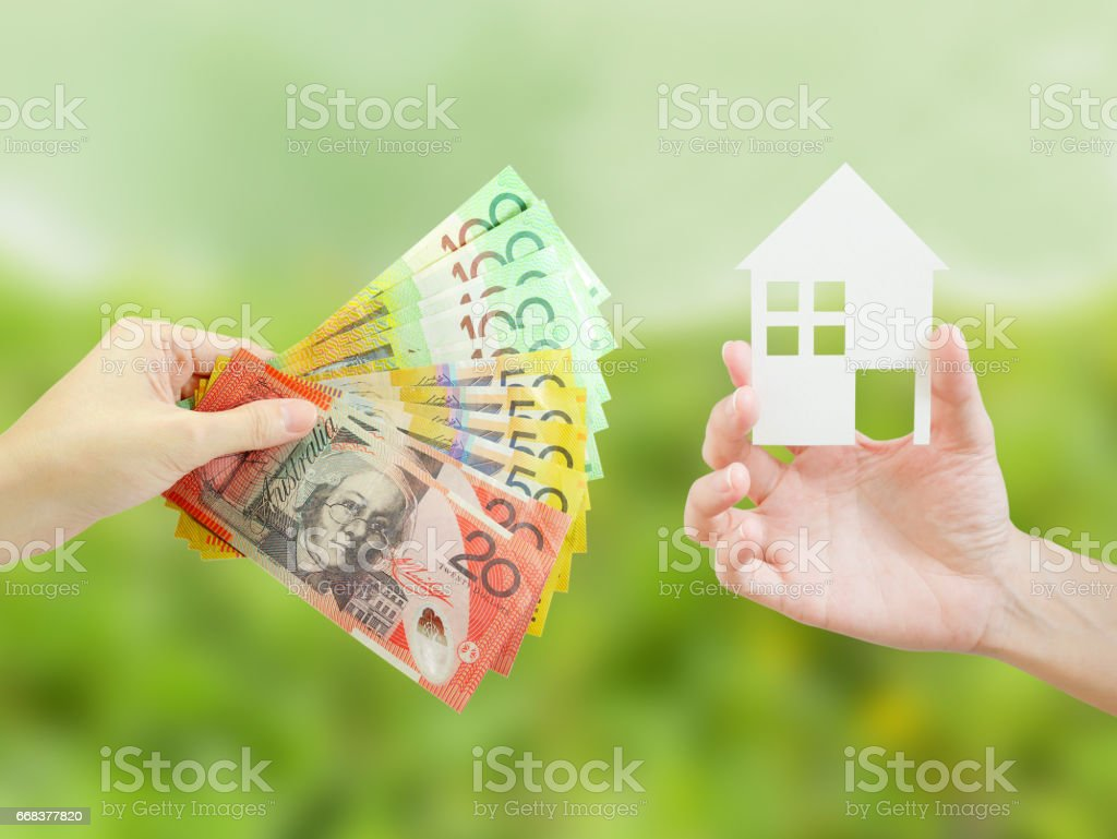 Client giving Australian money to property agent for buying house stock photo