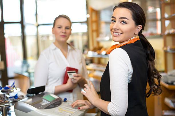 client in shop paying at cash register - verkoopster stockfoto's en -beelden