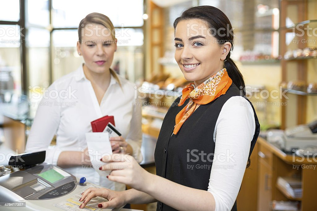 Client in shop paying at cash register stock photo