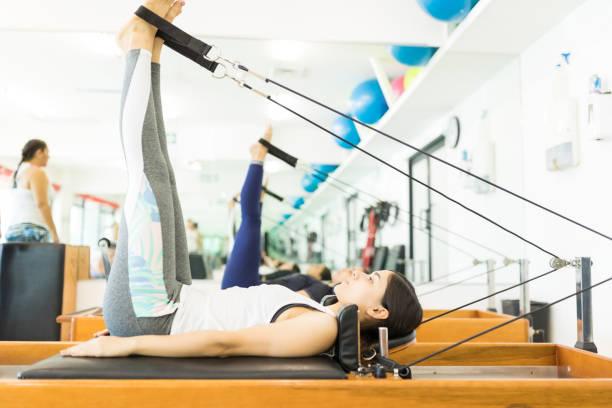 client maintaining her fitness while exercising on reformer machine - pilates zdjęcia i obrazy z banku zdjęć