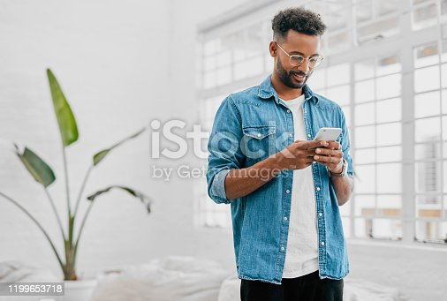 Shot of a young businessman using a smartphone in a modern office