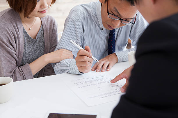 client signing a real estate contract in real estate agency - sign language stock photos and pictures