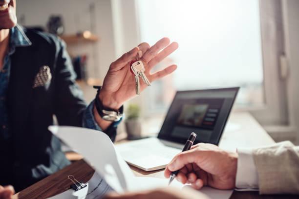 Kunden unterzeichnen Vertrag, während Immobilienmakler Schlüssel hält – Foto