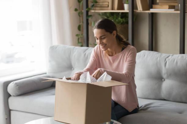 client woman sitting on couch unbox carton box feels satisfied - confezione foto e immagini stock