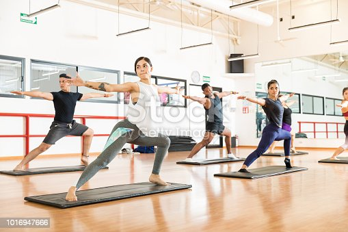 Clients performing Warrior II Pose on exercise mat in health club