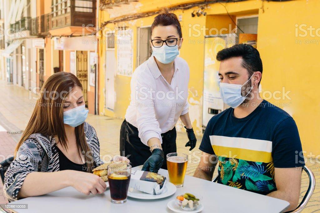 Clientes con máscaras en la terraza de un bar en España atendidos por un camarero con guantes y máscaras. Distanciamiento social - Foto de stock de Adulto libre de derechos