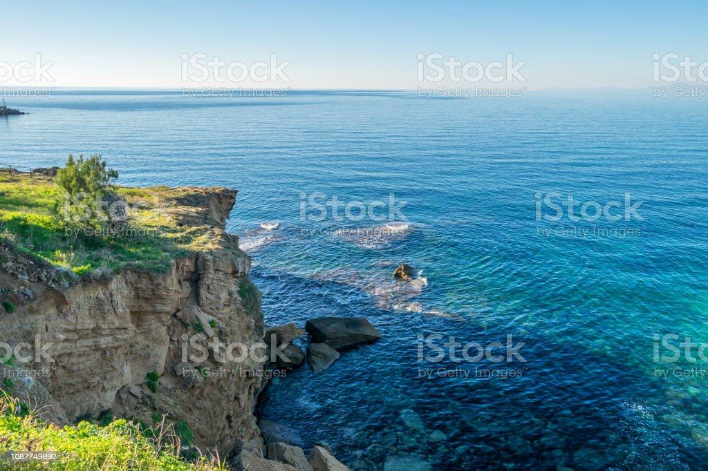 Cliff langs de blauwe Middellandse Zee op een zonnige dag aan de zuidelijke kust van het Italiaanse foto